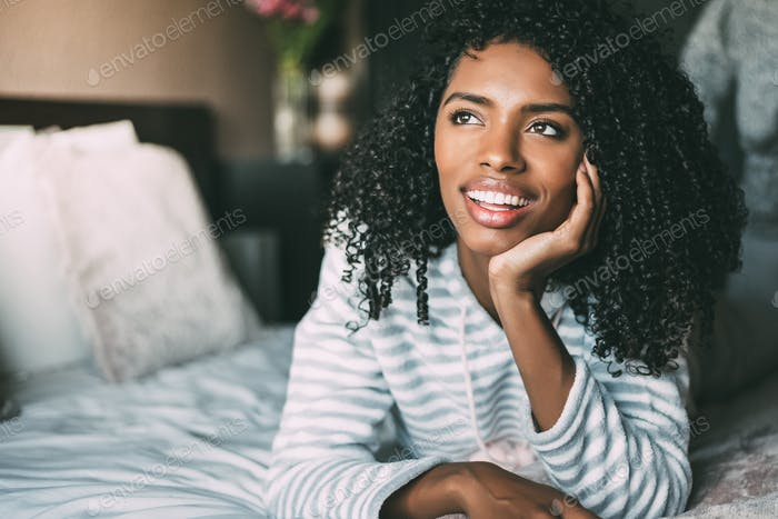 close up of a pretty black woman with curly hair smiling and lying on bed looking away
