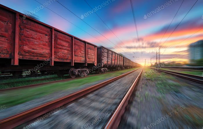 Moving freight train at sunset. Railroad and beautiful sky