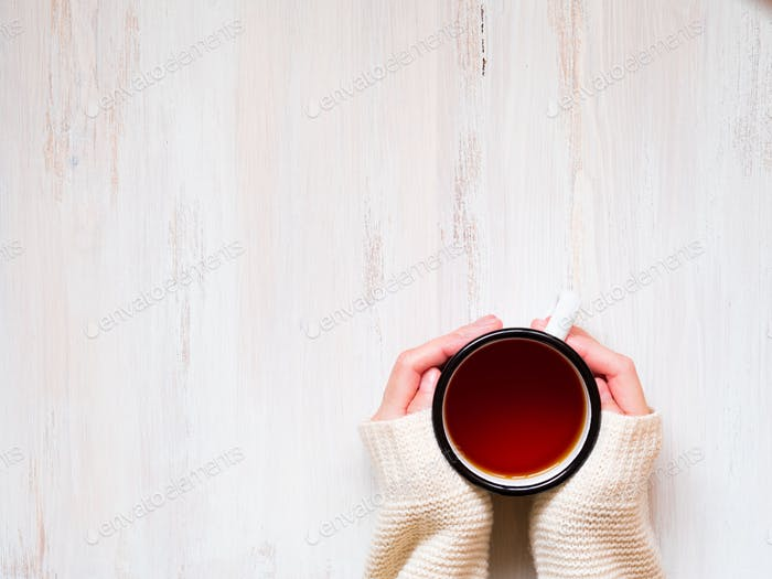 Female hands holding a mug of hot black tea.