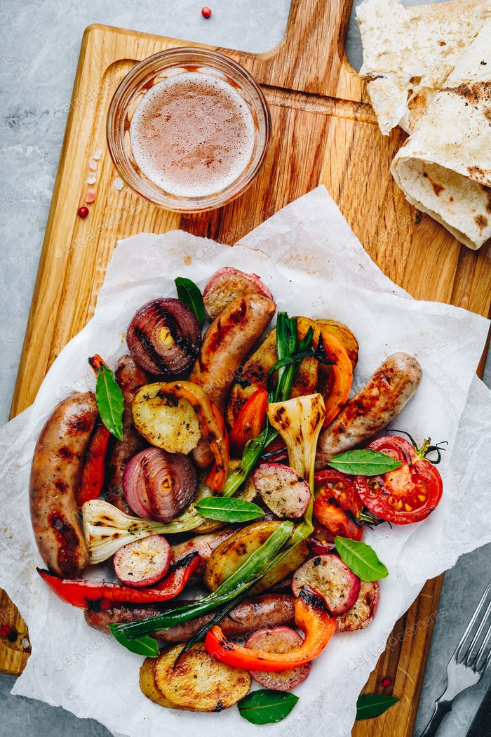 Grilled vegetables and sausages on wooden board