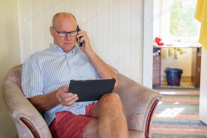 Senior Man mit Digital-Tablet und Telefon zu Hause