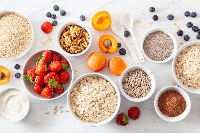 raw cereals, fruits and nuts for breakfast. Oatmeal flakes and steel cut, barley, walnut, chia