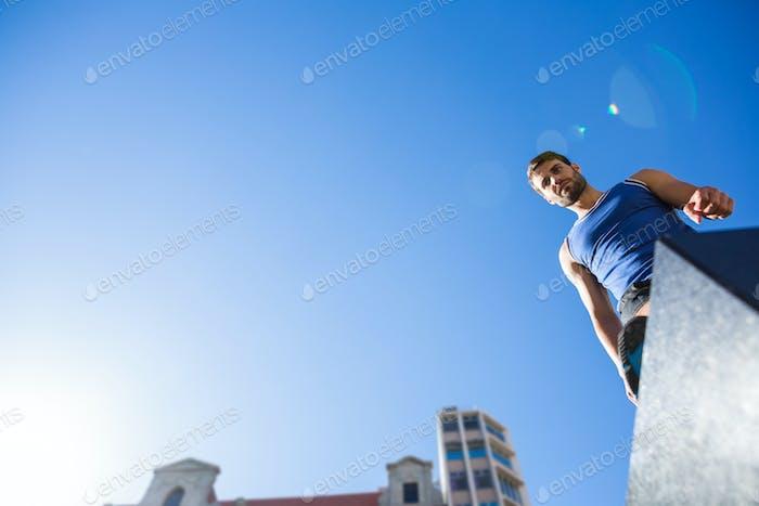 Schöner Athlet steht auf Säule gegen blauen Himmel in der Stadt