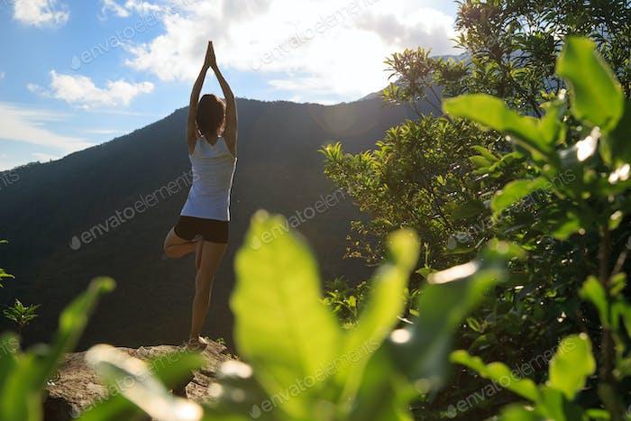 Yoga woman meditation on sunrise mountain top cliff edge