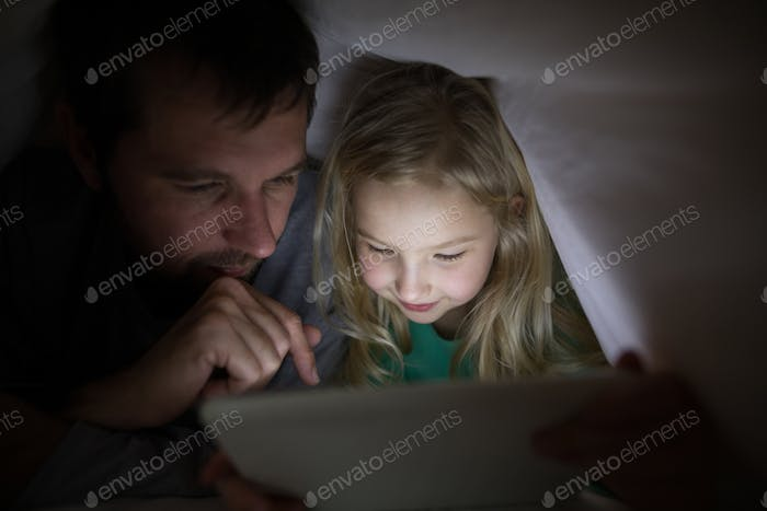 Father and daughter lying under blanket and using digital tablet