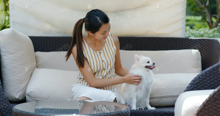 Woman play with her dog and sit at resort house