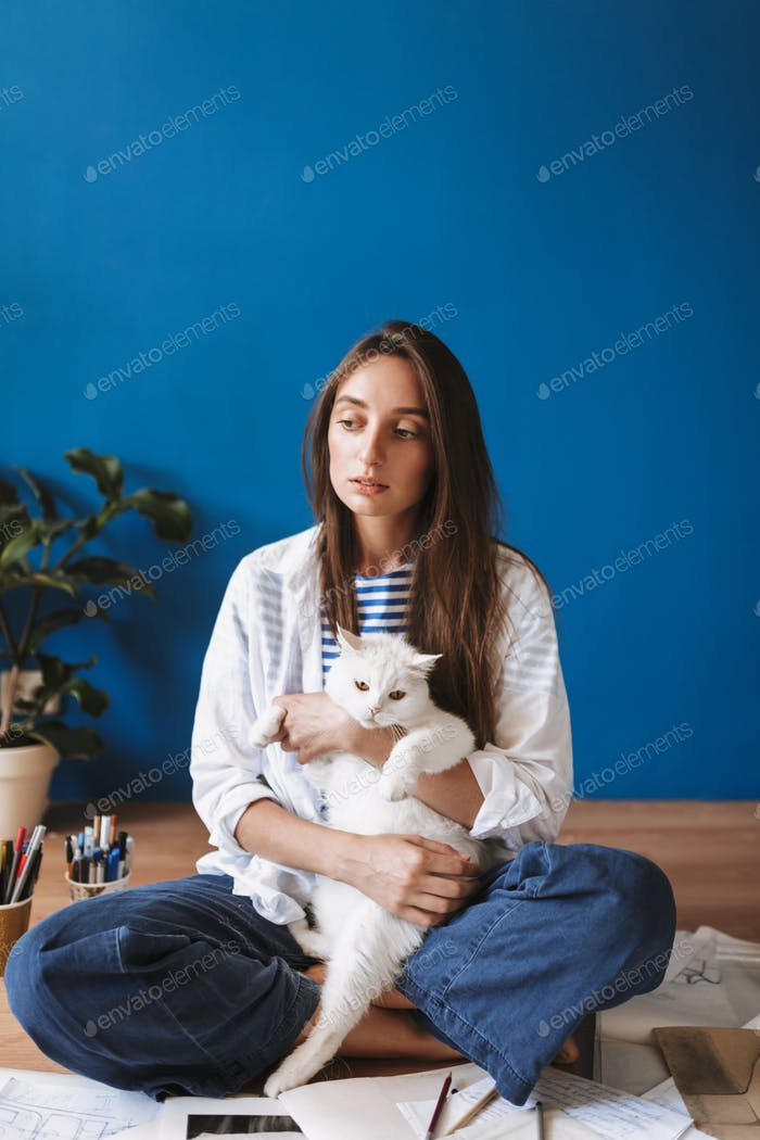 Thoughtful girl sitting on floor with sketches hugging white cat