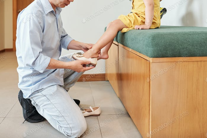 Helping daughter to wear shoes
