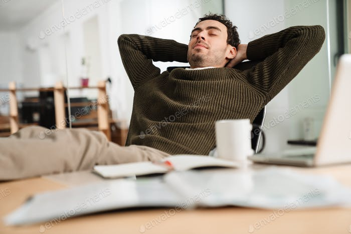 Happy businessman with hands behind head relaxing