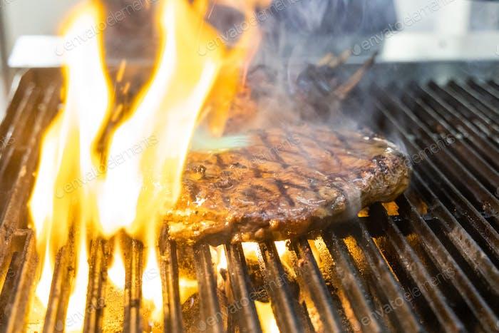 Beef ribeye steak being barbecue grilled in restaurant