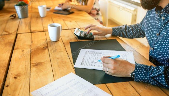 Asesor masculino llenando documentos fiscales en la oficina