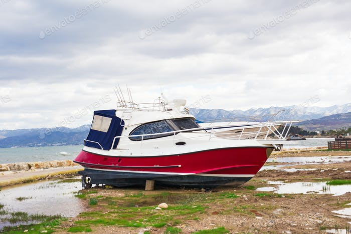 The yachts are aground in shallow sea water. Boat run aground in waterless pier or harbor.