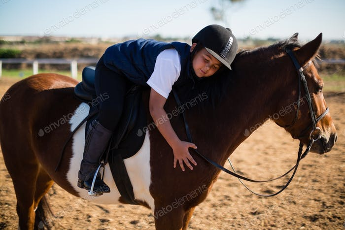 Smiling boy embracing the white horse in the ranch