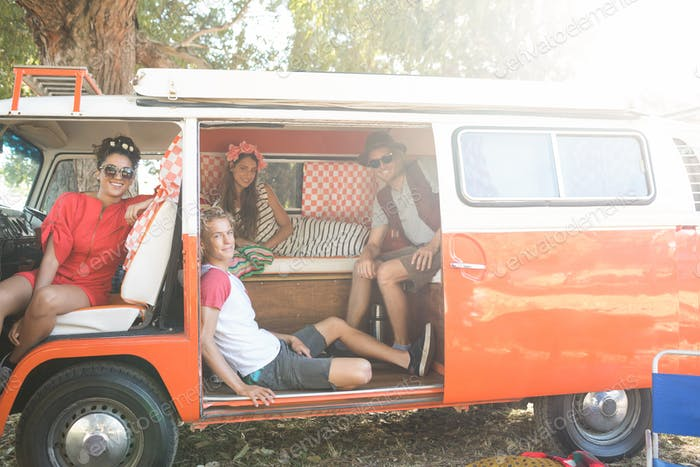 Portrait of friends sitting together in camper van