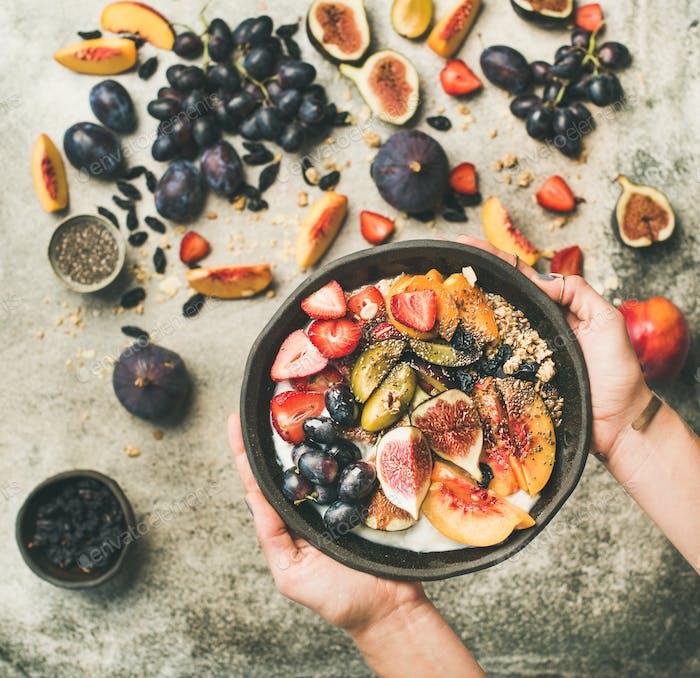Healthy breakfast bowl in hands of woman, top view