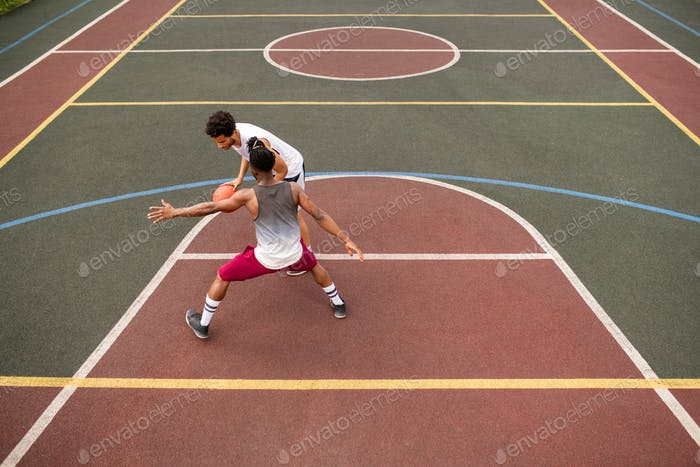 Young sportsman carrying ball while trying to throw it over his rival