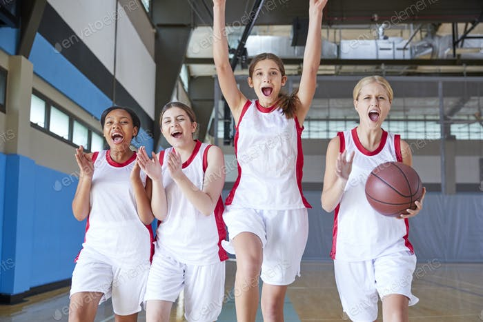 Portrait Of Female High School Basketball Team Celebrating On Court