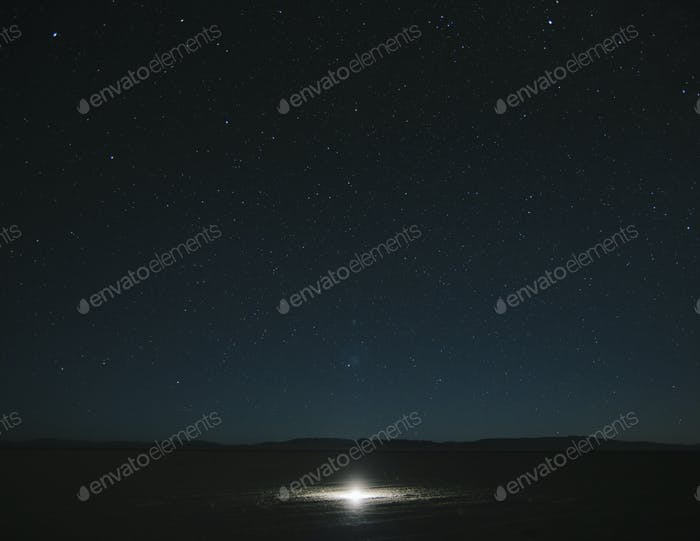 Glowing bright light on playa, night sky and Milky Way above, Black Rock Desert, Nevada