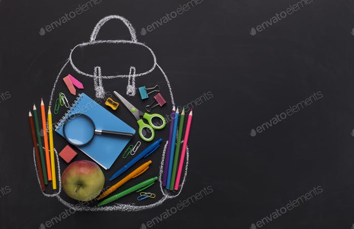Modern backpack with school stationery inside on black board