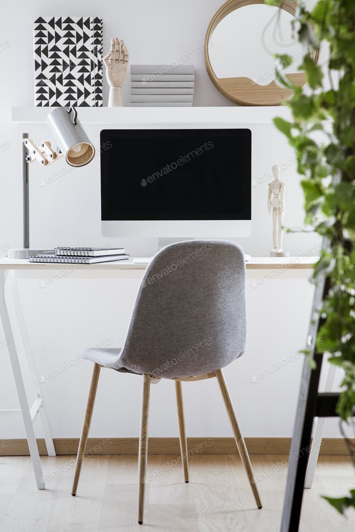 Grey chair at desk with lamp and desktop computer in simple whit