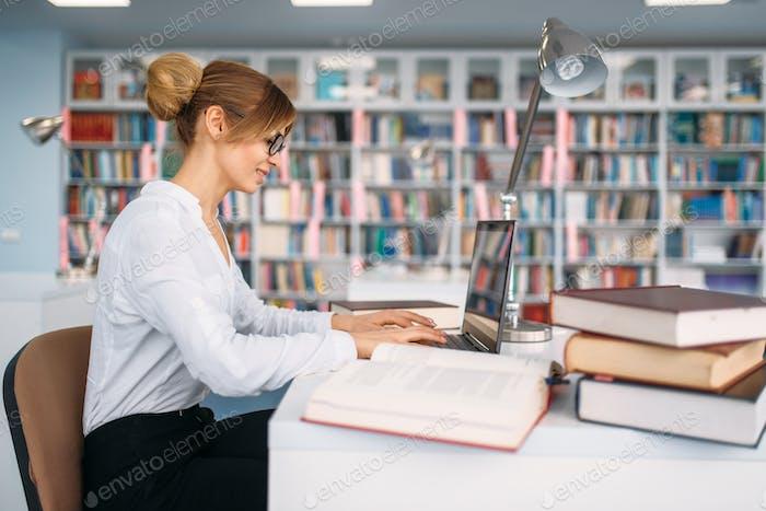 Studentin am Laptop in der Universitätsbibliothek