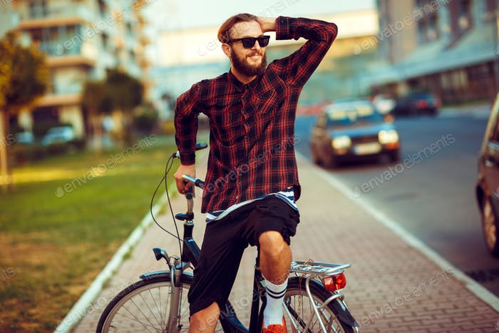 Young man in sunglasses riding a bike on city street