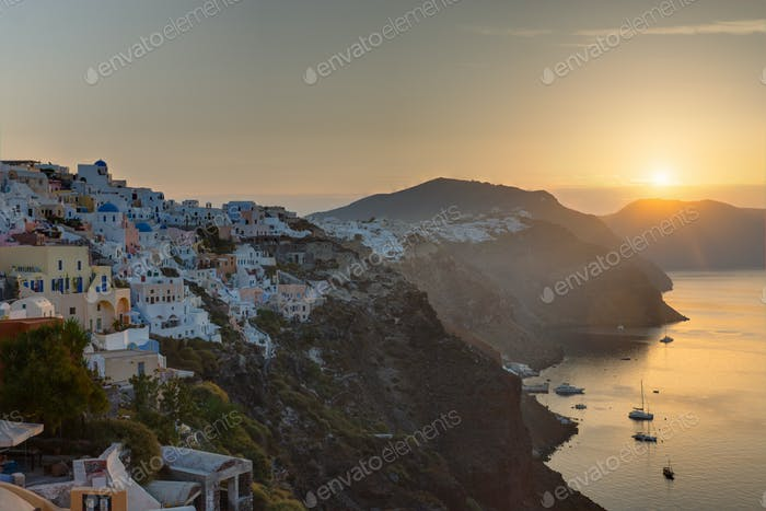 The sun rises over Oia