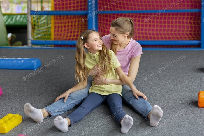 Happy mom with daughter hugging while sitting on floor at kids play centre