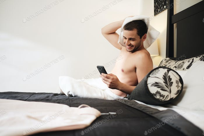 Gay Man Calling Partner On Mobile Phone In Hotel Room