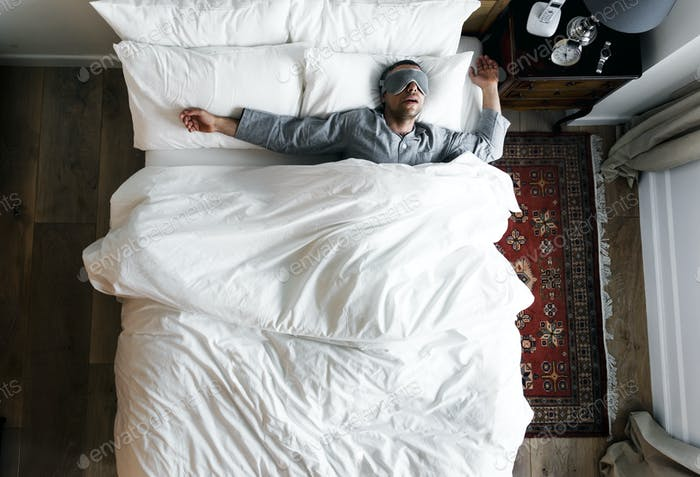 Man on bed sleeping with an eye cover
