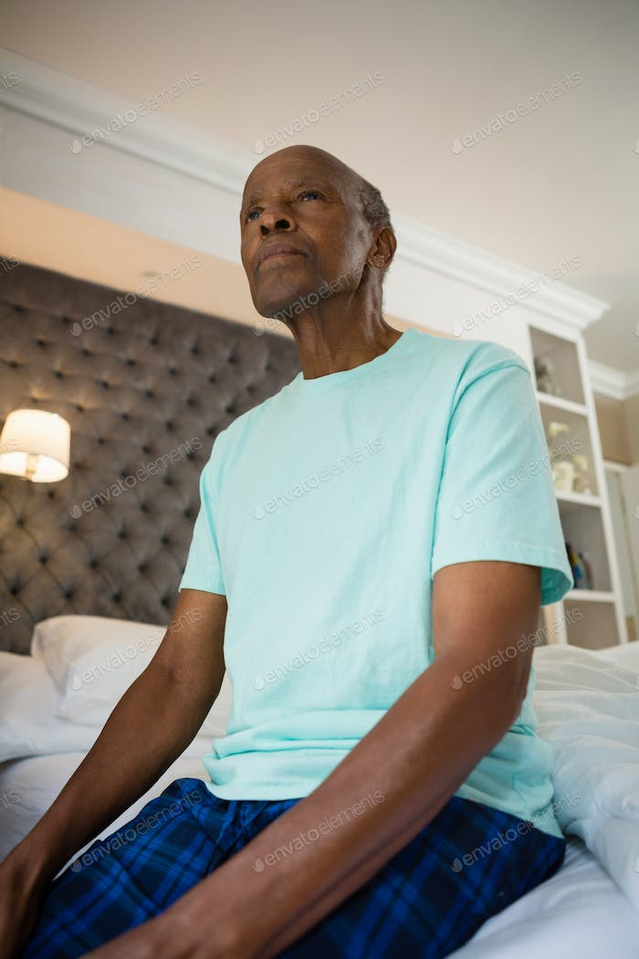 Thoughtful senior man sitting on bed at home