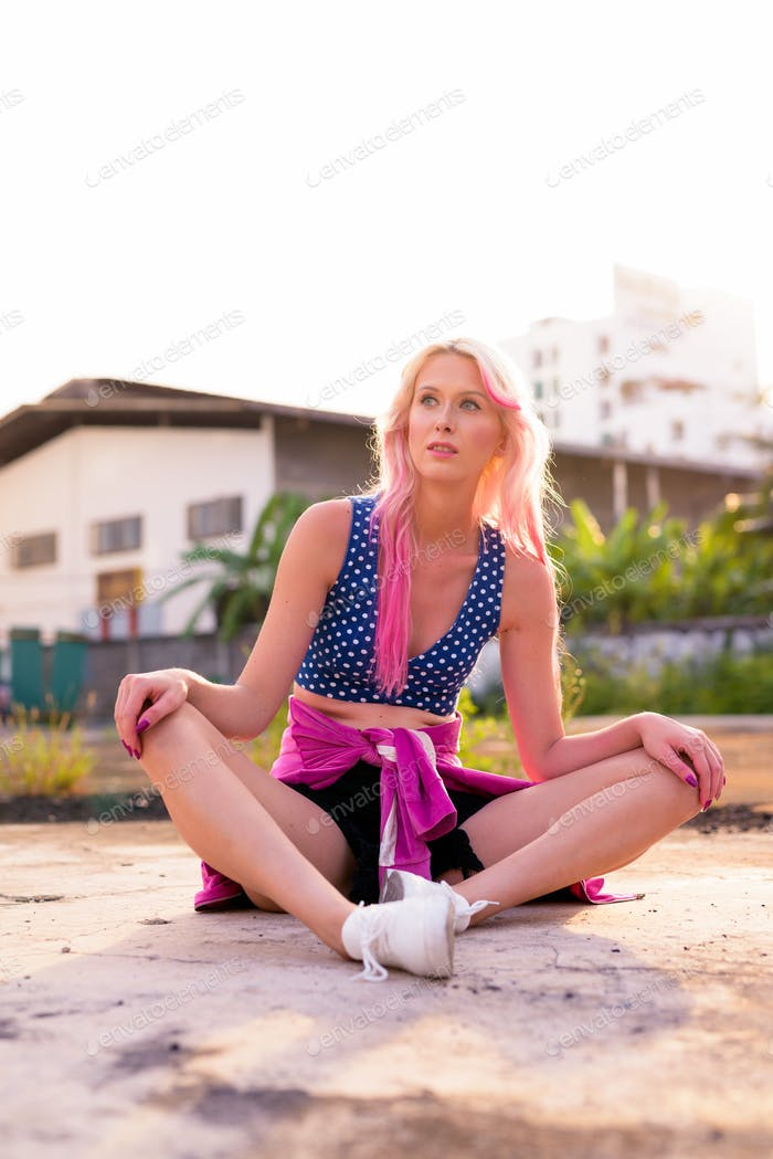 Full body shot of young beautiful blonde woman sitting in the streets outdoors