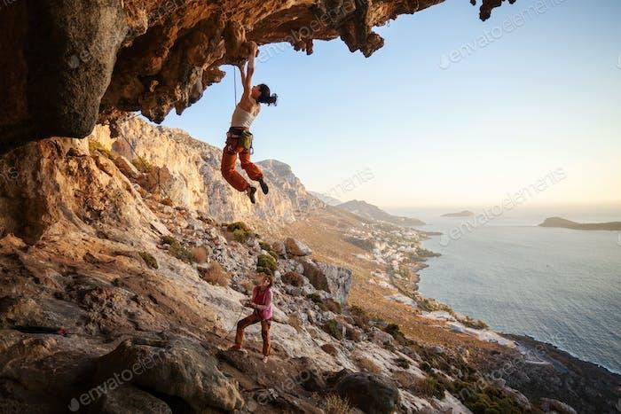 Junge Frau führen Klettern auf überhängenden Klippen