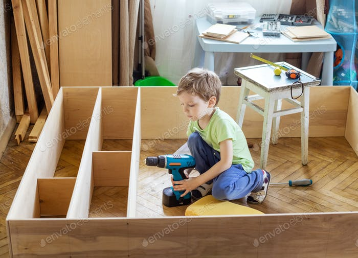 Young boy holding screwdriver while sitting on floor