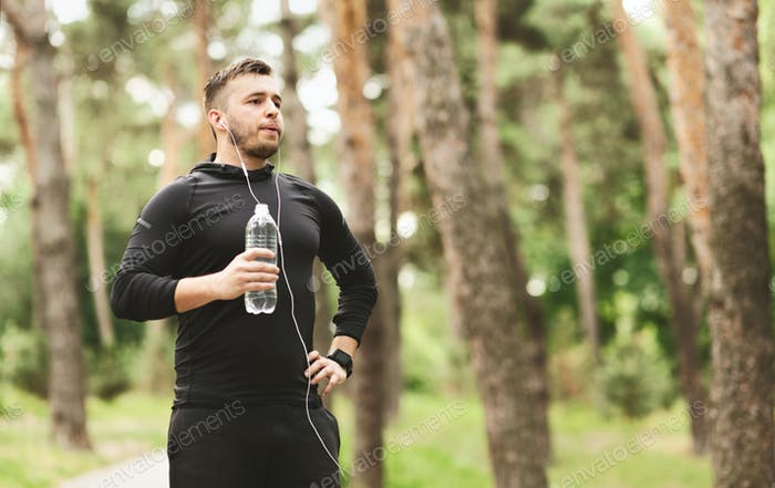 Man resting and drinking water after jogging in park