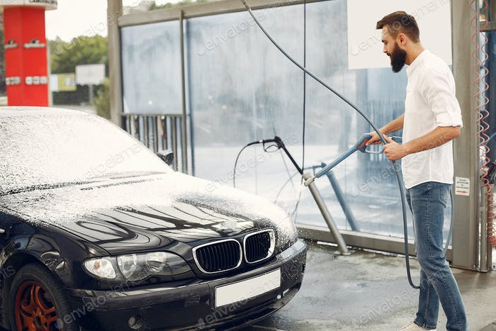 Man washing his car in a washing station