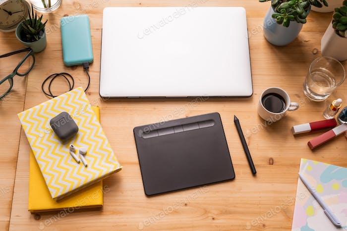 Notebooks mit schnurlosen Ohrhörern, gefaltetem Laptop, Pad mit Eingabestift usw. auf dem Tisch