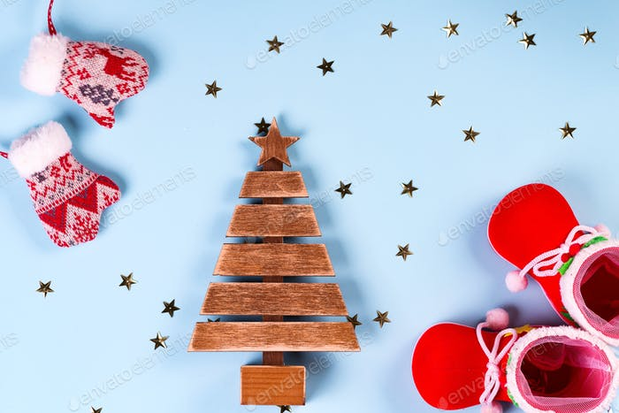 santa claus clothes with shoes and mittens on a blue background, wooden fir tree with stars on the