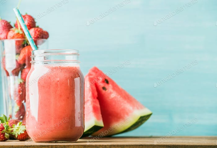 Freshly blended red fruit smoothie in glass jar with straw