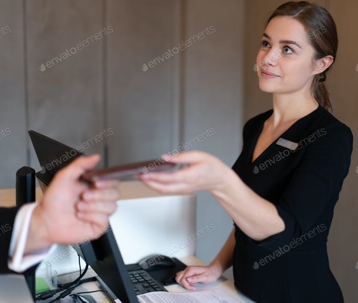 Female receptionist giving room key to businessman after arriving in hotel