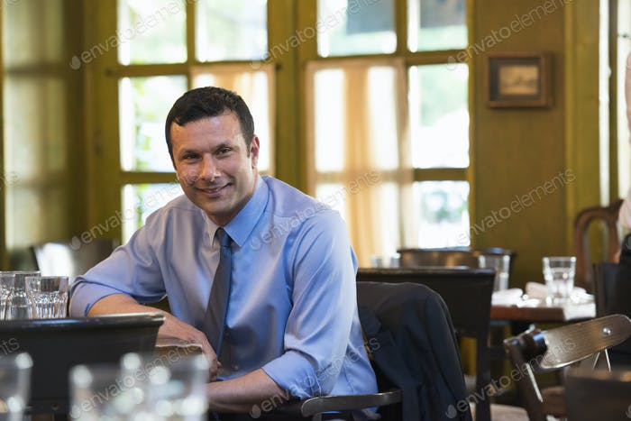 Business people outdoors. A latino man sitting at a table alone, relaxing.