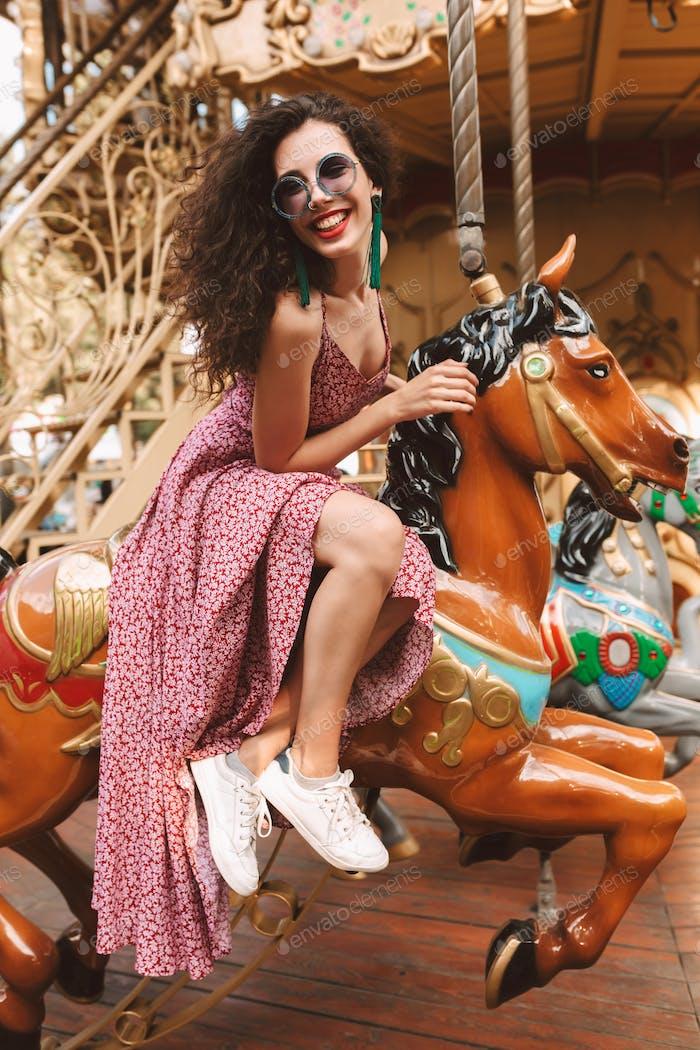 Schöne lächelnde Mädchen in Sonnenbrille und Kleid sitzen auf Karussell Pferd glücklich im Vergnügungspark