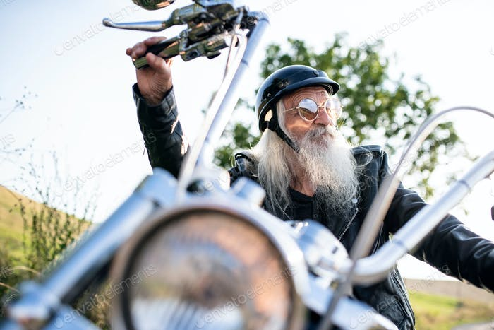 Senior man traveller with motorbike and sunglasses in countryside