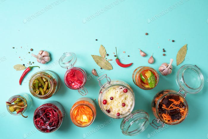 Assortment of various fermented and marinated food over blue background, copy space. Top view