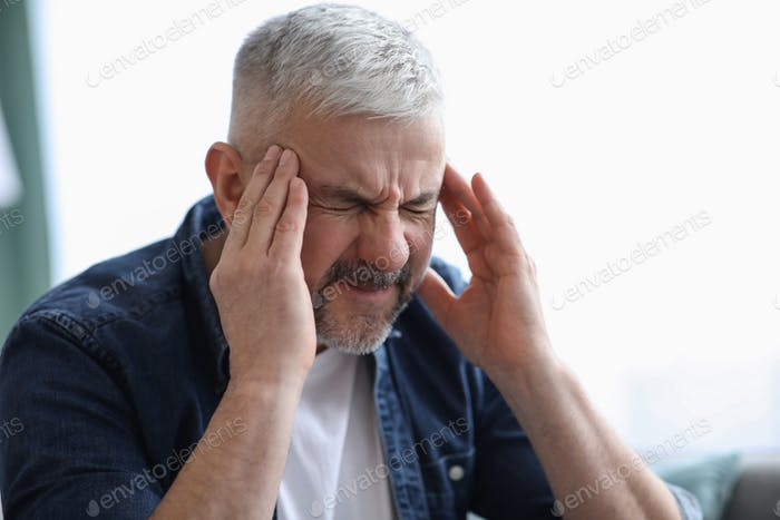 Closeup of mature grey-haired man suffering from headache