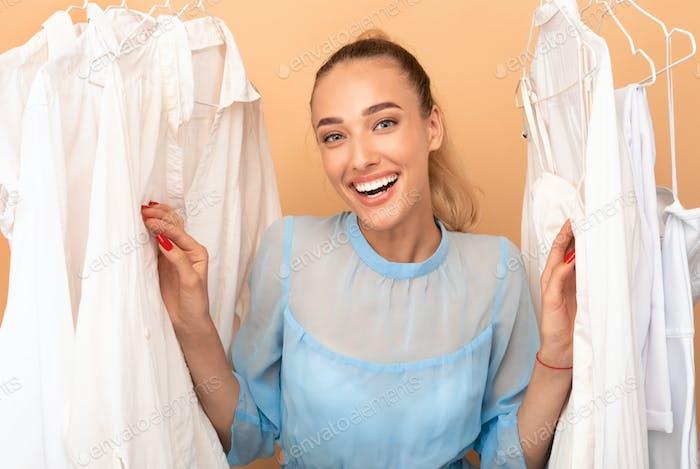 Porträt der glücklichen Frau Wahl Kleidung stehen in der Nähe von Rack