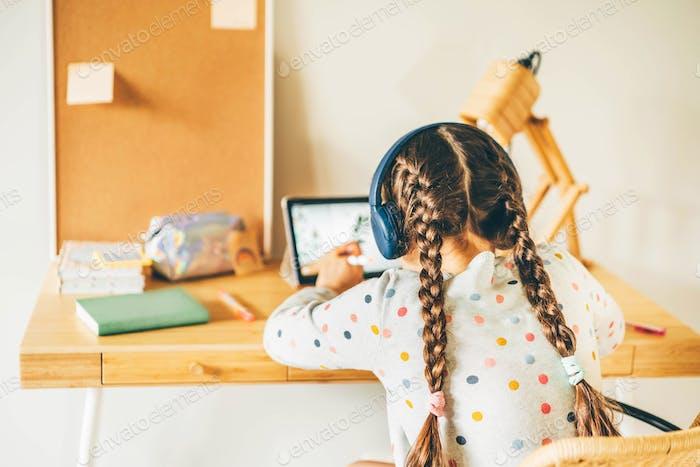 Little girl at home with digital tablet doing homework.