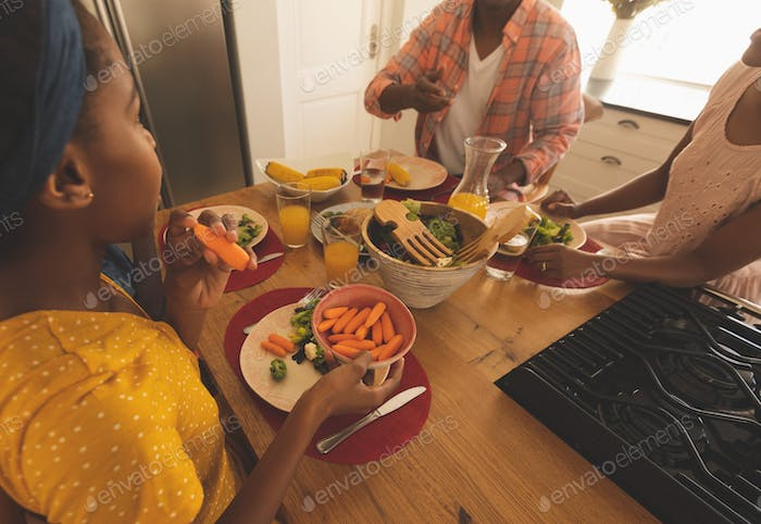 Side view of African American family having food at dining table in comfortable home