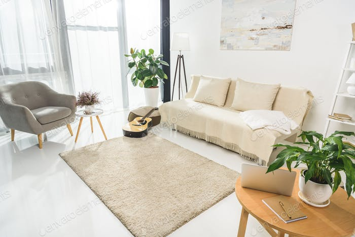 Minimalistic living room interior with white furniture and plants, lit by bright sunlight