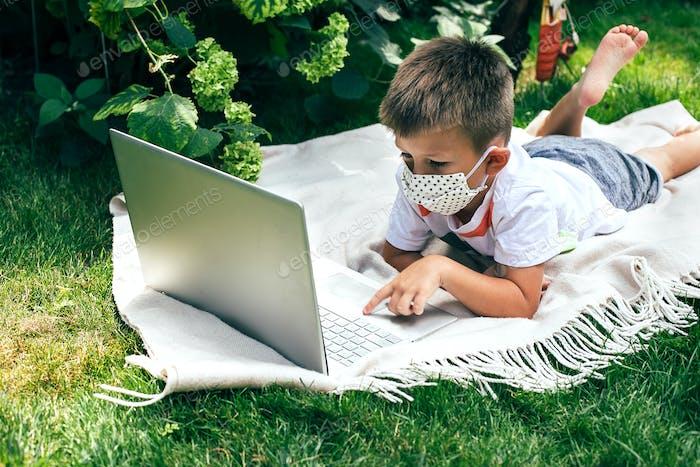 Kleiner Junge in einer Maske, auf Plaid auf dem Gras mit einem Laptop während der Quarantänezeit liegend.